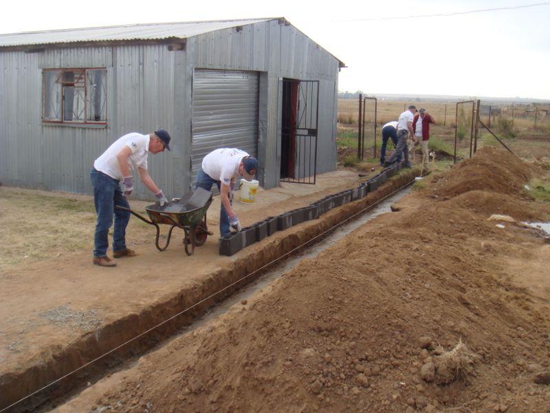 De eerste stenen voor de te bouwen muur staan gereed.