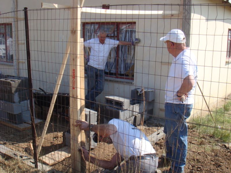 Deze ploeg is reeds aan de bouw van de garage begonnen.  Hans en Jan van Unen kijken toe hoe Cees de maat neemt.