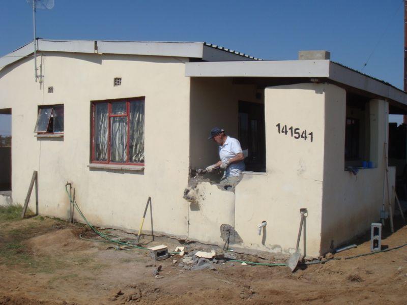 Voor geweld zal alles zwichten. Dirk Maarseveen heeft een grote moker en maakt een doorgang van het `oude` gebouw naar de nieuwe kerkzaal.