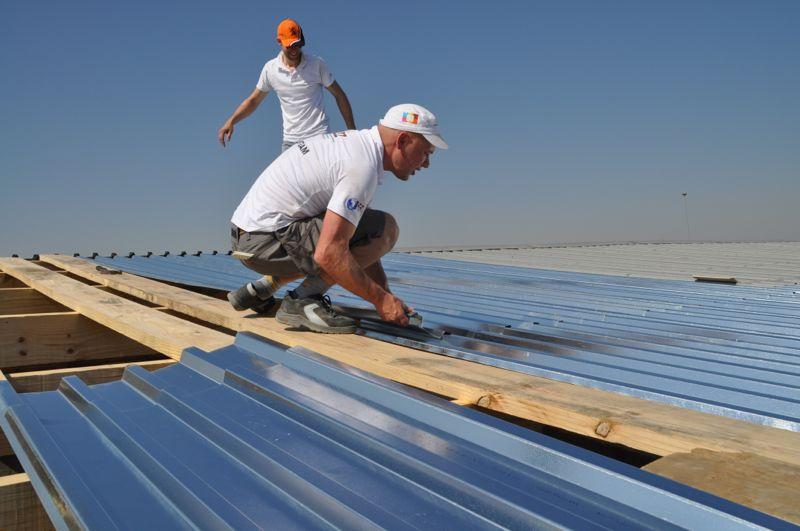 De dakdekkers Robert en Kuno hebben geen enkele moeite daar boven op het dak.