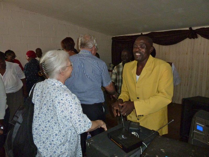 mw. Merel Reitsema feliciteert de voorzitter van de kerkenraad broeder Kunene.